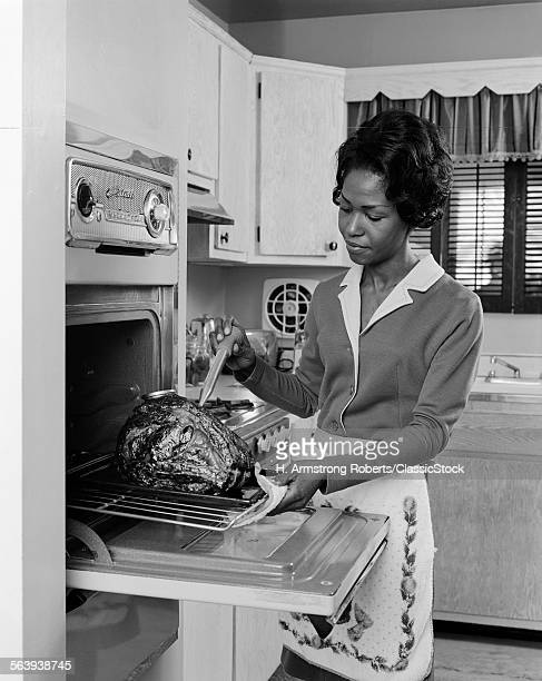 1960s 1970s BLACK WOMAN AFRICAN AMERICAN OVEN BASTING A ROAST BEEF