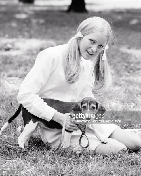 1960s 1970s Blonde Teen Girl Woman With Her Hair In Pony Tails Sitting In Grass With Beagle Dog On Leash Both Looking At Camera.
