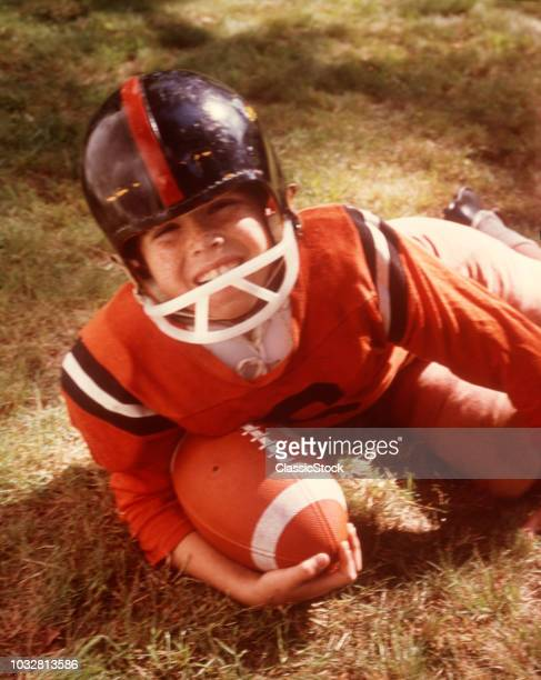 1960s 1970s BOY LYING IN GRASS CLUTCHING FOOTBALL WEARING FULL FOOTBALL GEAR LOOKING AT CAMERA