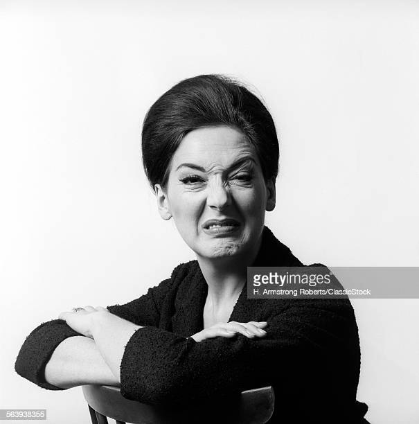 1960s 1970s BRUNETTE MIDDLE AGED WOMAN MAKING FUNNY FACE LOOKING AT CAMERA WITH WRINKLED NOSE AND ARMS FOLDED ON BACK OF CHAIR