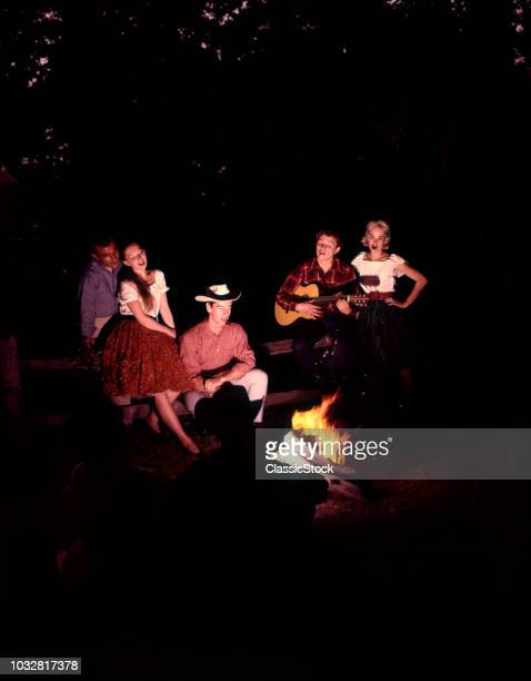 1960s 1970s COUPLES MEN WOMEN SINGING COUNTRY AND WESTERN MUSIC SITTING AROUND CAMPFIRE AT NIGHT