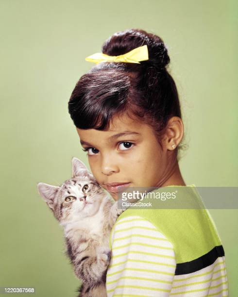 1960s 1970s cute young african american girl looking at camera holding hugging loving kitten