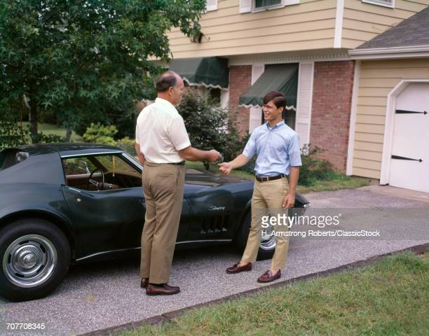 1960s 1970s FATHER HANDING TEENAGE SON KEYS TO CORVETTE STINGRAY AUTOMOBILE