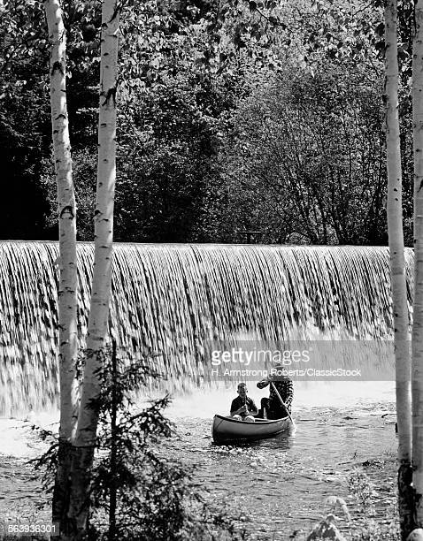 1960s 1970s FATHER SON IN CANOE IN FRONT OF WATERFALL WITH FATHER PADDLING SON FISHING