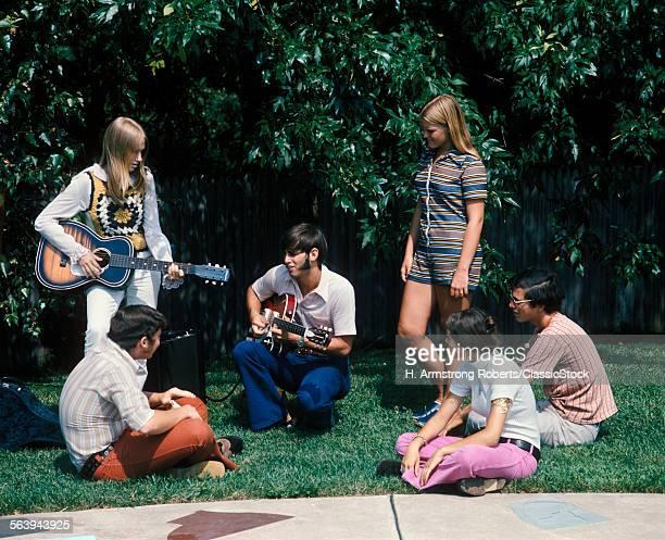 1960s 1970s GROUP OF 6 TEENS BOYS GIRLS IN BACKYARD SUMMER 1 BOY 1 GIRL PLAYING GUITAR SIDEBURNS FASHION