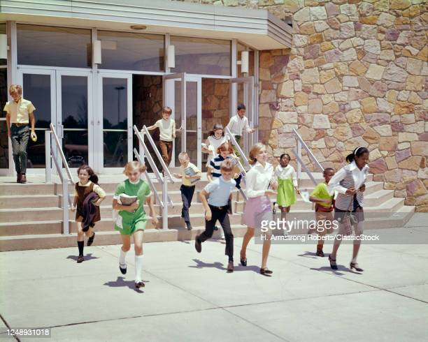 1960s 1970s Group Of Ethnically Diverse Kids Running Out Of School Building At End Of Day Or End Of School Year Summer Break