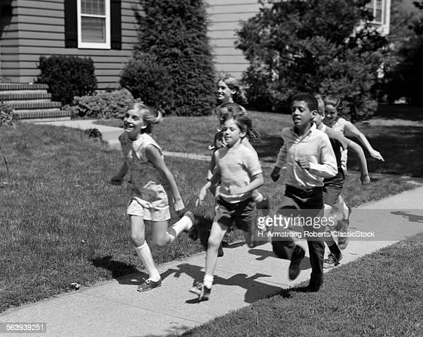 1960s 1970s GROUP OF KIDS RUNNING DOWN SUBURBAN SIDEWALK