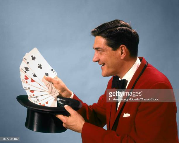 1960s 1970s MAN MAGICIAN RED SUIT BOW TIE PULLING OVERSIZE PLAYING CARDS OUT OF TOP HAT