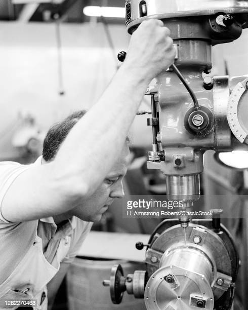 1960s 1970s Man Skilled Industrial Machinist Operating A Precision Drill Press In A Machine Shop