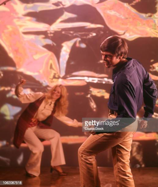 1960s 1970s MAN WOMAN DANCING WITH PSYCHEDELIC BACKGROUND