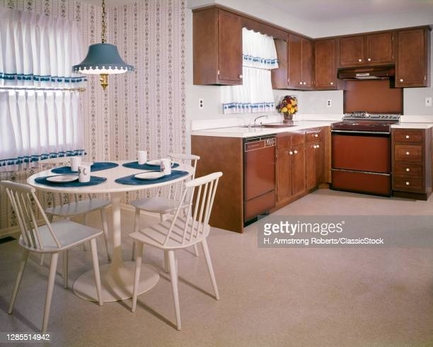 1960s 1970s Model Showroom Kitchen With Dated Brown Appliances Dark Wood Cabinets And White Dinette Set