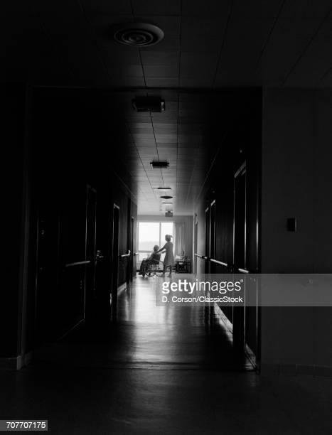 1960s 1970s NURSE PUSHING ELDERLY FEMALE PATIENT DOWN DARK HOSPITAL HALLWAY IN WHEELCHAIR