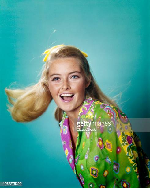 1960s 1970s Portrait Smiling Happy Young Woman Swinging Blonde Hair Looking At Camera Bright Blue Eyes Wearing Print Shirt