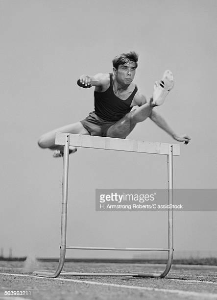 1960s 1970s RUNNING MAN JUMPING OVER HURDLE