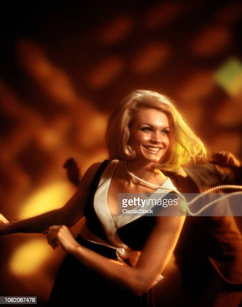 1960s 1970s SMILING BLOND WOMAN DANCING IN DISCO STRAND OF PEARLS SWINGING