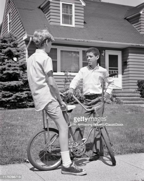 1960s 1970s TWO PRETEEN BOYS ONE AFRICAN AMERICAN AND THE OTHER CAUCASIAN WITH BICYCLE TALKING TOGETHER ON SUBURBAN SIDEWALK