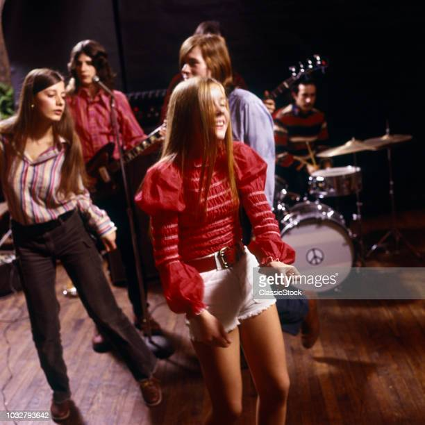 1960s 1970s TWO TEENAGE GIRLS AND A BOY DANCING IN FRONT OF ROCK & ROLL BAND GIRL WEARING HOT PANTS FASHION PEACE SIGN ON DRUM