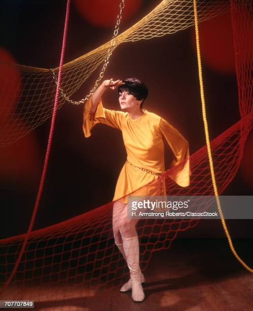 1960s 1970s YOUNG WOMAN IN SHORT GOLD TUNIC DRESS DANCING AMONG NETS AND ROPES