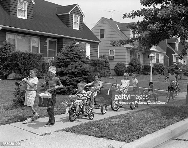 1960s 4th OF JULY BIKE PARADE OF BOYS & GIRLS LED BY BUGLER & DRUMMER WITH BANDAGED HEAD BIKES ALL DECORATED WITH AMERICAN FLAGS