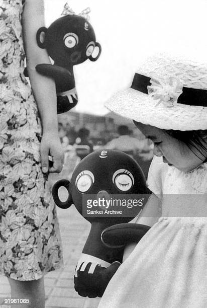 A girl holds a Dakkochan doll in the 1960s in Japan