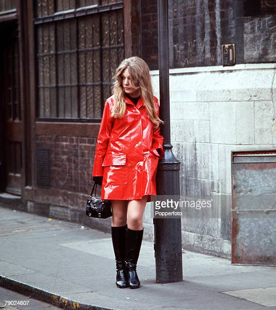 1960s A portrait of a woman standing on a street next to a lamppost wearing a red PVC jacket and kneehigh black boots