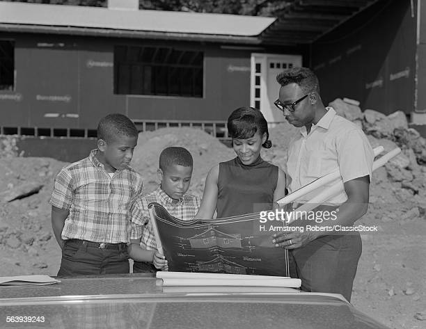 1960s AFRICAN AMERICAN FAMILY LOOKING AT BLUEPRINTS NEW HOUSE CONSTRUCTION