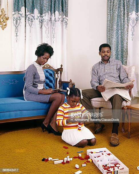 1960s AFRICAN AMERICAN FAMILY MOTHER FATHER SITTING READING LIVING ROOM GIRL DAUGHTER PLAYING ON FLOOR WITH LEGO TOYS