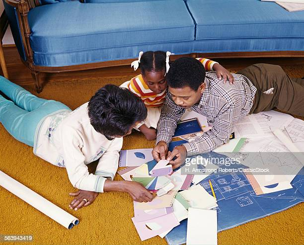 1960s AFRICAN AMERICAN FAMILY LYING ON FLOOR LOOKING OVER BLUEPRINTS NEW HOUSE PLANS PAINT CHIPS