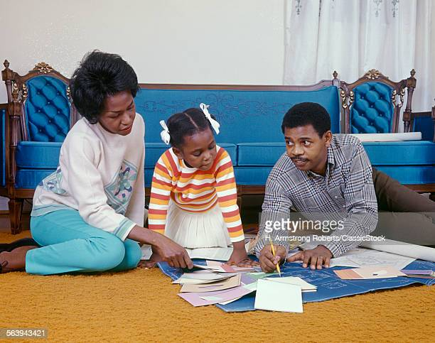 1960s AFRICAN AMERICAN FAMILY MOTHER FATHER DAUGHTER SITTING ON LIVING ROOM FLOOR WITH BLUEPRINTS PAINT CHIPS