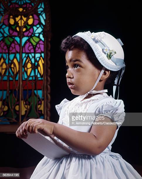 1960s AFRICAN AMERICAN GIRL BY STAINED GLASS WINDOW IN CHURCH HOLDING BIBLE WEARING HAT