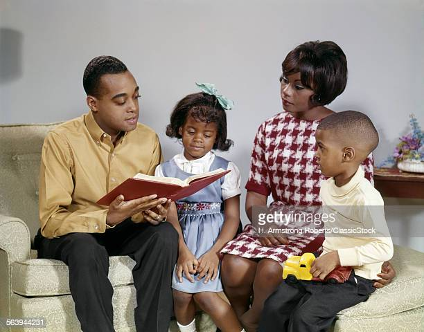 1960s AFRICAN AMERICAN FATHER READING A BOOK TO FAMILY