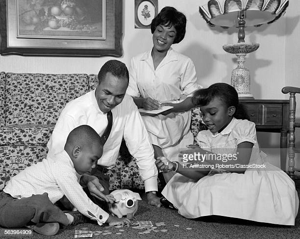 1960s AFRICAN AMERICAN FAMILY ON LIVING ROOM FLOOR COUNTING CHANGE IN PIGGY BANK