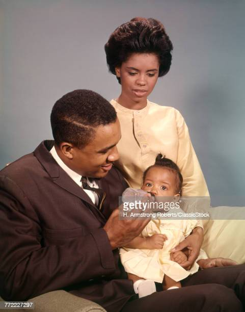 1960s AFRICAN AMERICAN FAMILY FATHER FEEDING BABY BOTTLE MOTHER SITTING ON ARM OF CHAIR