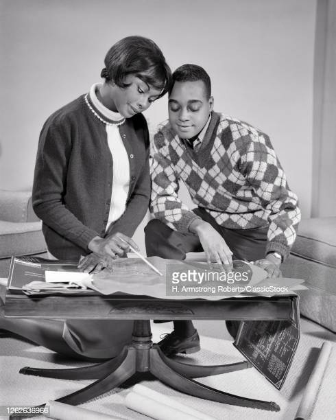 1960s African-American Couple Man Woman Husband And Wife Heads Together Going Over Plans Blueprints For New Home