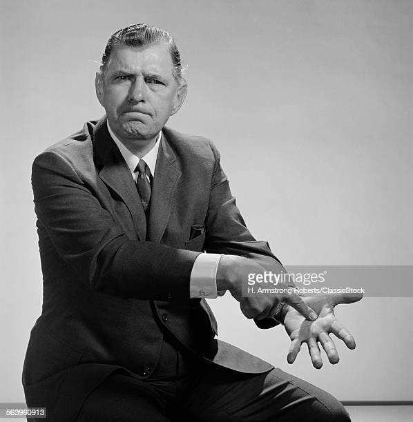 1960s ANGRY MAN POINTING TO PALM OF HIS HAND