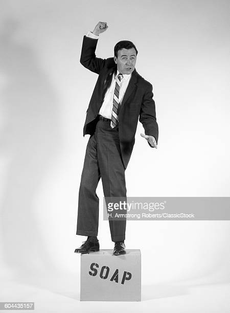 1960s ANGRY MAN IN SUIT ON SOAPBOX RAISING FIST IN ANGER LOOKING AT CAMERA