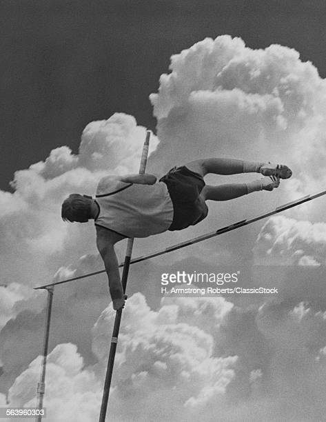 1960s ANONYMOUS POLE VAULTER MAN SILHOUETTED AGAINST SKY AND CLOUDS