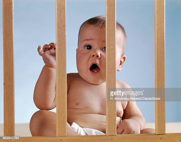 1960s BABY IN CRIB OR PLAYPEN LOOKING THROUGH BARS ALARMED EXPRESSION