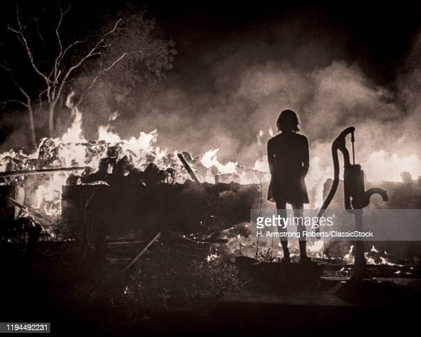 1960s BACK OF SILHOUETTED ANONYMOUS YOUNG WOMAN LOOKING AT AFTERMATH REMNANTS OF TOTAL DISASTER DEVASTATING RURAL HOUSE FIRE