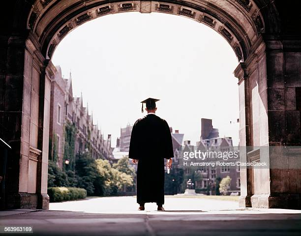 1960s BACK VIEW MALE GRADUATE WEARING CAP AND GOWN STANDING IN CAMPUS ARCHWAY UNIVERSITY OF PENNSYLVANIA PHILADELPHIA USA