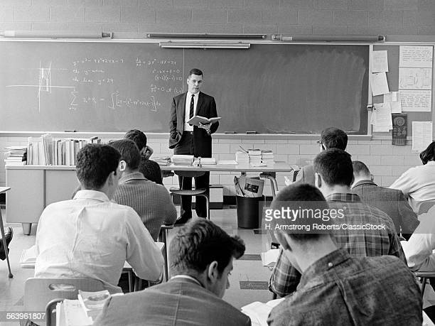 1960s BACK VIEW OF CLASSROOM WITH TEACHER STANDING BEHIND DESK WITH BOOK IN HAND EXPLAINING GRAPHED EQUATION ON BLACKBOARD