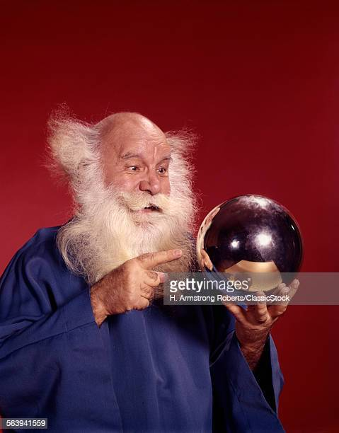 1960s BALDING WHITE HAIRED MAN IN ROBE LOOKING AT SILVER BALL HE IS HOLDING STUDIO