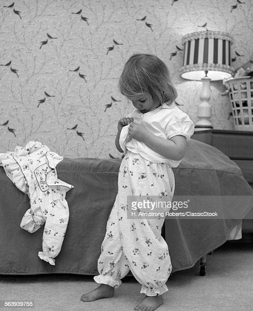 1960s BEDTIME LITTLE BLOND GIRL IN PAJAMA BOTTOMS UNBUTTONING SHIRT TO PUT ON PAJAMA TOP
