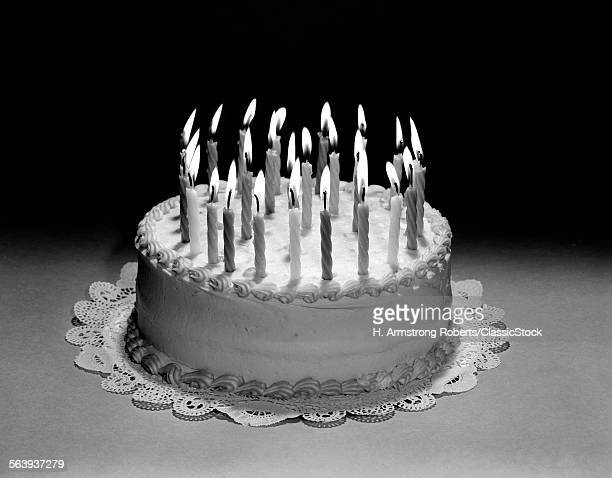 1960s BIRTHDAY CAKE STILL LIFE WITH MANY LIT CANDLES ON TOP OF PAPER DOILY
