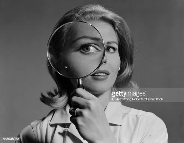 1960s BLOND WOMAN MAGNIFYING GLASS HELD UP TO AND ENLARGING ONE EYE
