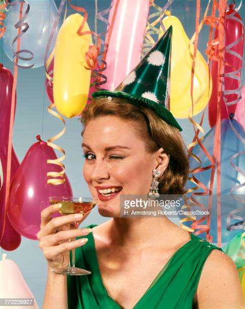 1960s BLOND WOMAN CELEBRATING NEW YEARS WEARING PARTY PAPER HAT DRINKING CHAMPAGNE LOOKING AT CAMERA WINKING EYE