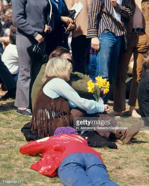 1960s BLONDE WOMAN IN FRINGED VEST HOLDING YELLOW DAFFODILS AMIDST CROWD 1969 PEACE RALLY FAIRMONT PARK PHILADELPHIA PA USA