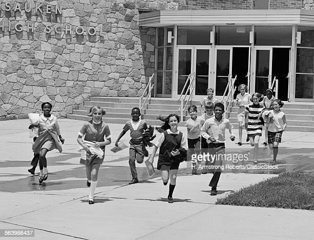1960s BOY AND GIRL STUDENTS RUNNING OUT OF SCHOOL BUILDING