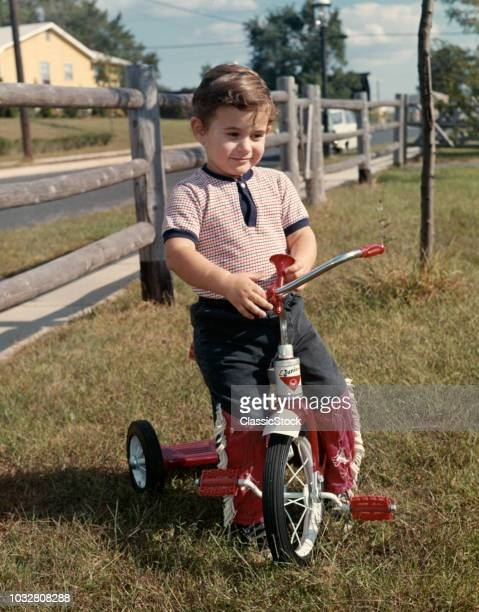 1960s BOY BACKYARD BY WOODEN FENCE SITTING ON RED TRICYCLE HORN ON HANDLEBAR TEE SHIRT JEANS WITH RED COWBOY FRINGE