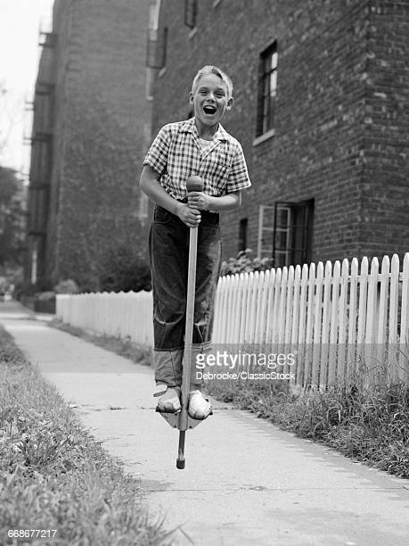 1960s BOY ON POGO STICK ON...